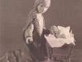 Holzfigur Frau mit Kind in Wiege.png